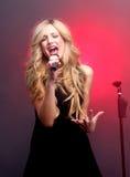 在阶段唱歌的美丽的白肤金发的摇滚明星 免版税库存图片