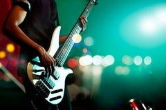 在阶段的吉他弹奏者低音背景,五颜六色,软的焦点和迷离的 免版税库存照片
