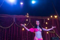 在阶段的火舞蹈家旋转的火焰状警棒 免版税库存图片