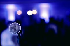 在阶段的话筒在蓝色被弄脏的背景的音乐会前 免版税库存照片
