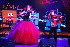 在阶段,传神红发小提琴手玛丽亚Bessonova儿子孪生 小提琴三重奏两几代红色火热的音乐家 免版税库存图片