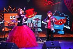 在阶段,传神红发小提琴手玛丽亚Bessonova儿子孪生 小提琴三重奏两几代红色火热的音乐家 免版税库存照片