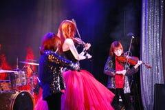 在阶段,传神红发小提琴手玛丽亚Bessonova儿子孪生 小提琴三重奏两几代红色火热的音乐家 库存照片