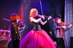 在阶段,传神红发小提琴手玛丽亚Bessonova儿子孪生 小提琴三重奏两几代红色火热的音乐家 库存图片
