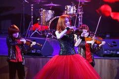 在阶段,传神红发小提琴手玛丽亚Bessonova儿子孪生 小提琴三重奏两几代红色火热的音乐家 免版税图库摄影