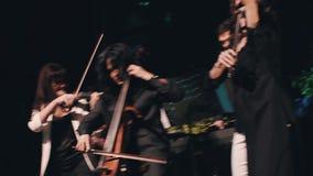 在阶段,阶段的三位女性小提琴手的非常情感讲话 在阶段的凉快的摇滚乐队 摇滚乐队 股票视频
