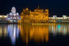 在阿姆利则、旁遮普邦、印度、最神圣的象和锡克教徒的宗教崇拜地方的金黄寺庙  照亮夜, r 免版税库存照片