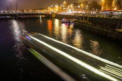 在阿姆斯特丹夜运河的巡航小船  免版税库存照片