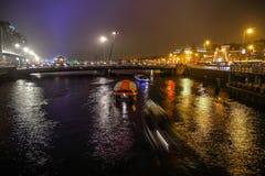 在阿姆斯特丹夜运河的巡航小船  图库摄影