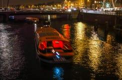 在阿姆斯特丹夜运河的巡航小船  免版税图库摄影