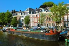 在阿姆斯特丹渠道的老小船有背景的典型的房子的,阿姆斯特丹,荷兰 免版税库存照片
