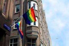 在阿姆斯特丹街道上的彩虹旗子 免版税库存图片
