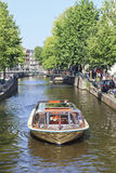 在阿姆斯特丹运河传送带的游览小船。 免版税库存图片