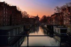 在阿姆斯特丹运河桥梁的红色天空 免版税库存照片