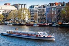 在阿姆斯特丹运河的旅游小船 免版税库存图片