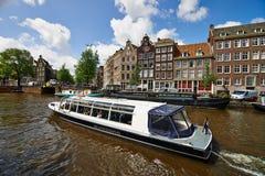 在阿姆斯特丹运河的游览小船 库存照片