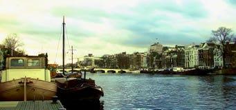 在阿姆斯特丹运河的老驳船在荷兰 免版税库存照片