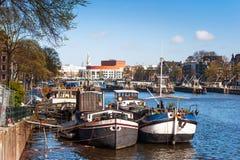 在阿姆斯特丹运河的被停泊的小船 免版税库存照片