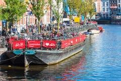 在阿姆斯特丹骑自行车在一条老游览小船的停车处 免版税库存照片