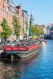 在阿姆斯特丹骑自行车在一条老游览小船的停车处 免版税库存图片
