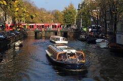 在阿姆斯特丹,荷兰游览小船和路面电车 图库摄影