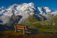 在阿尔卑斯多雪的山的长凳视图 图库摄影