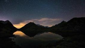 在阿尔卑斯的满天星斗的天空和猎户星座时间间隔,在积雪覆盖的山土坎之外,在田园诗高山湖的反射 股票录像