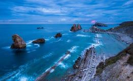 在阿尔尼亚多岩石的海滩的多云日出在坎塔布里亚 库存照片