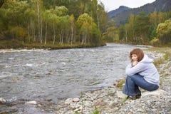在阿尔泰山河附近的微笑的妇女 秋天 库存照片