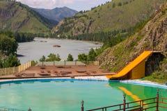 在阿尔泰山的室外水池与一条黄色水滑道在 库存照片