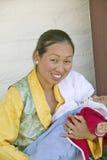 在阿弥陀佛援权佛教仪式期间,传统礼服的西藏妇女抱孩子,凝思登上在Ojai,加州 免版税库存图片