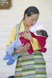 在阿弥陀佛援权佛教仪式期间,传统礼服的西藏妇女抱孩子,凝思登上在Ojai,加州 免版税库存照片