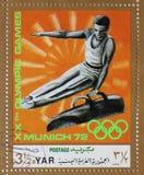 在阿拉伯也门共和国打印的邮票在慕尼黑显示鞍马的,奥林匹克体操运动员 免版税库存照片
