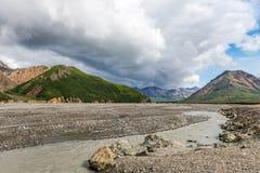 在阿拉斯加山脉的暴风云浮游物和平的石渣 库存图片