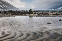 在阿拉斯加海滩的起波纹的沙子样式与在岩石岸的遥远的波浪 免版税库存照片