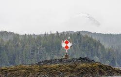在阿拉斯加的海岸的红色和空白定位标记 免版税库存照片