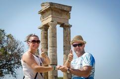 在阿波罗古老废墟前面的愉快的夫妇在罗得岛 库存照片