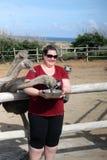 在阿鲁巴驼鸟农场的妇女哺养的驼鸟 库存照片