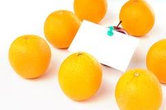 在附注桔子纸张里面的苹果组 库存照片
