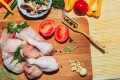在附近厨房用桌、菜和厨房辅助部件谎言的粗暴鸡肉 免版税库存照片