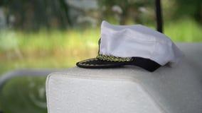 在附近的白色上尉帽子在小船方向盘 与风船的夏时假期在开阔水域,在游艇的上尉帽子 股票视频