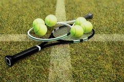 在附近的网球拍在一个绿色法院的黄色球 免版税库存照片