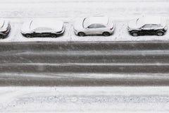 在降雪下的三辆汽车在路停放 免版税图库摄影