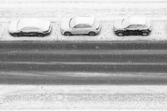 在降雪下的三辆汽车在路停放 图库摄影