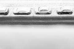 在降雪下的四辆汽车在路停放 免版税图库摄影