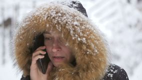 在降雪下的妇女身分使用一个手机叫和使用互联网 股票录像