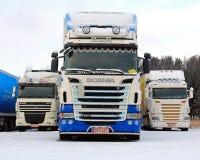 在降雪的三辆长的运输卡车 免版税库存照片