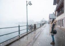 在降雪的妇女身分在Hallstatt 免版税库存照片