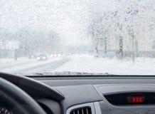 在降雪的都市风景从汽车 库存照片