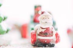 在降雪背景的一陶瓷圣诞老人圣诞快乐文本 可爱的圣诞快乐和新年快乐在降雪 库存照片